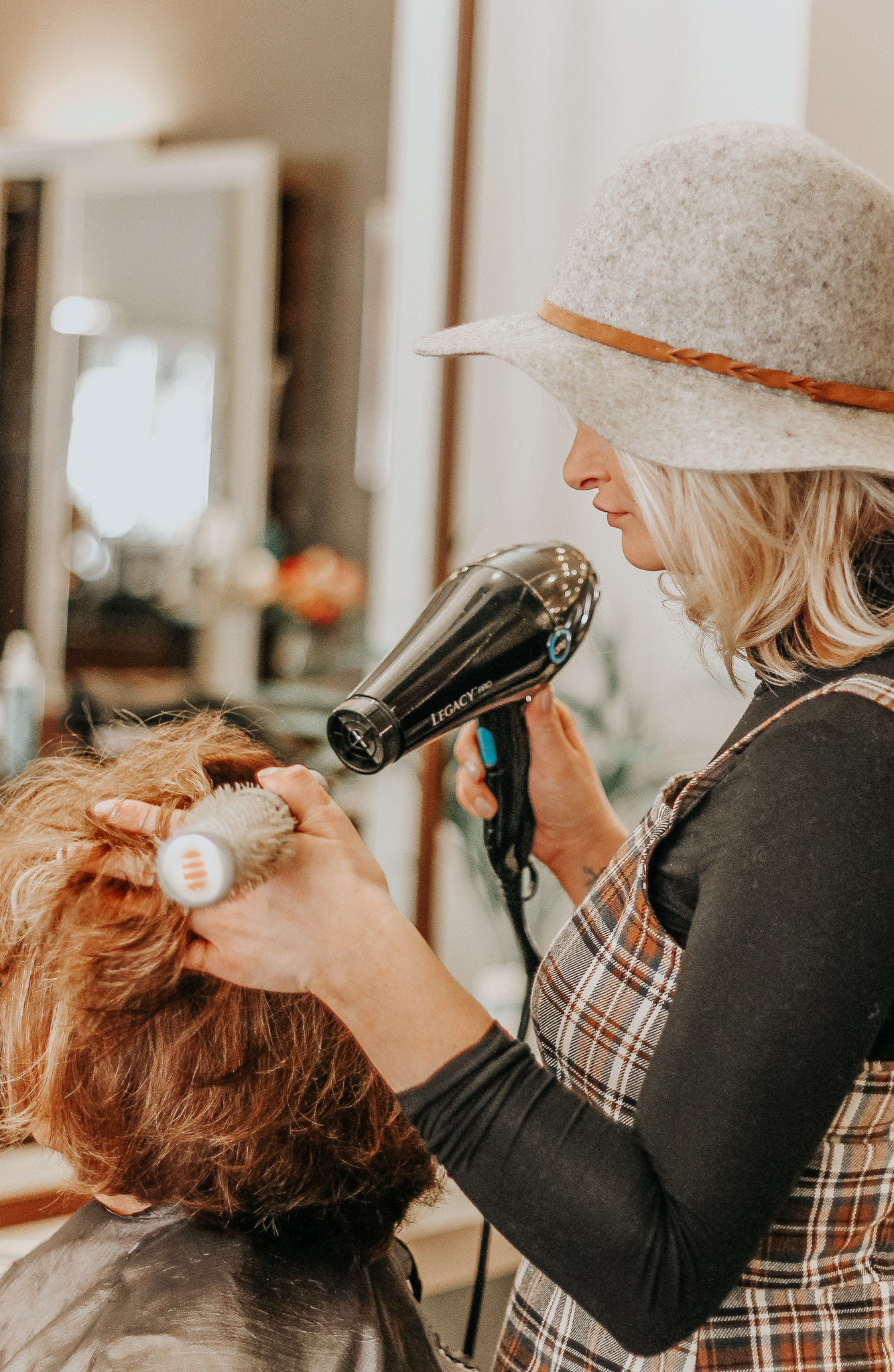 Stylist blow drying hair at this Omaha Hair Salon